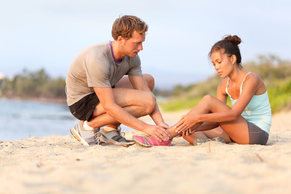 woman with twisted sprained ankle. asian fitness female model sitting on beach sand getting help from caucasian male touching her ankle.