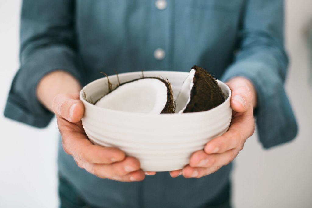 man holding bowl of halved coconut