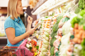 woman looking over grocery list in supermarket