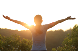 woman raising arms into sunlight