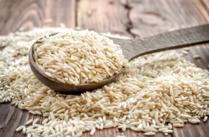 brown rice on wooden table and spoon