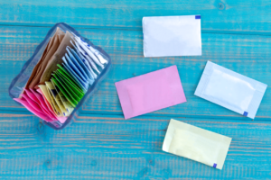 Packets of artificial sweeteners in glass container with individual packets sitting on bright blue wooden table