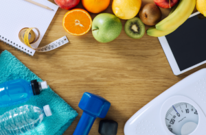 dumbbells, white scale, towels, fruit, tape measure and digital tablet on a wooden table, top view